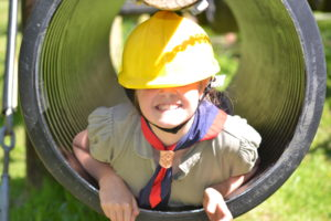 young person in a large tube and wearing helment and smiling